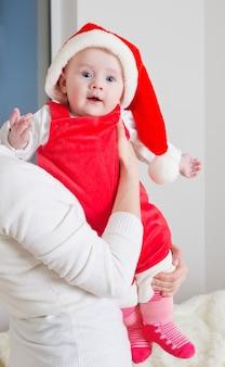 Mãe e bebê com chapéu vermelho de natal