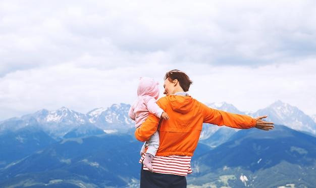 Mãe e bebê com montanhas em um fundo. família passa as férias de verão nas dolomitas, itália, europa. vista de bruneck e pustertal do cume da kronplatz.