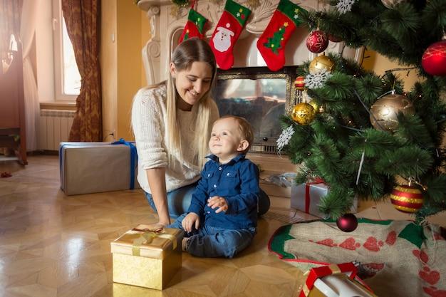 Mãe e bebê com presentes de natal no chão da sala de estar