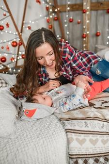 Mãe e bebê deitam-se em uma cama de ano novo. garotinho da mamãe. mãe e filho em casa.