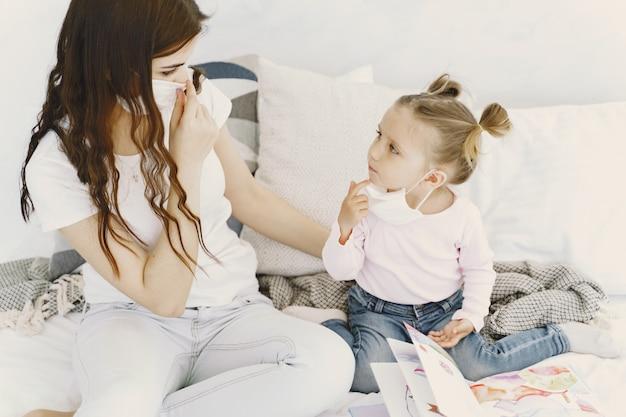 Mãe e bebê em casa com máscaras médicas