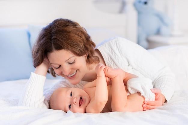 Mãe e bebê em uma cama branca
