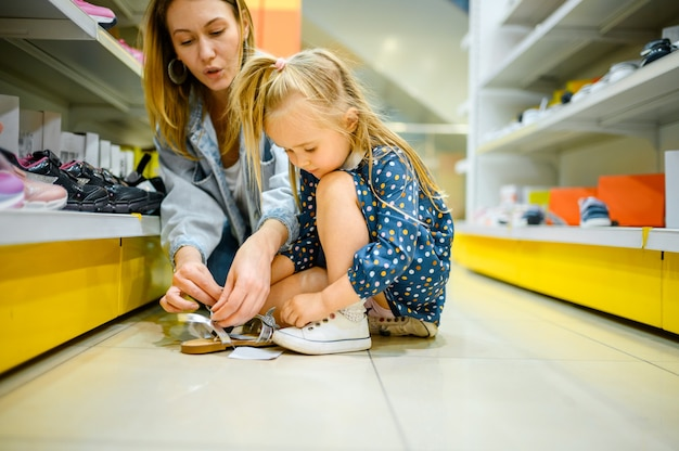 Mãe e bebê experimentando sapatos em loja infantil