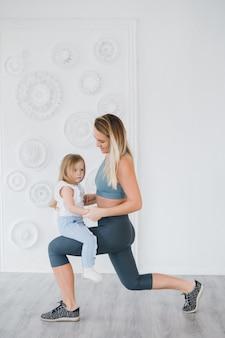 Mãe e bebê fazem exercícios juntos no ginásio