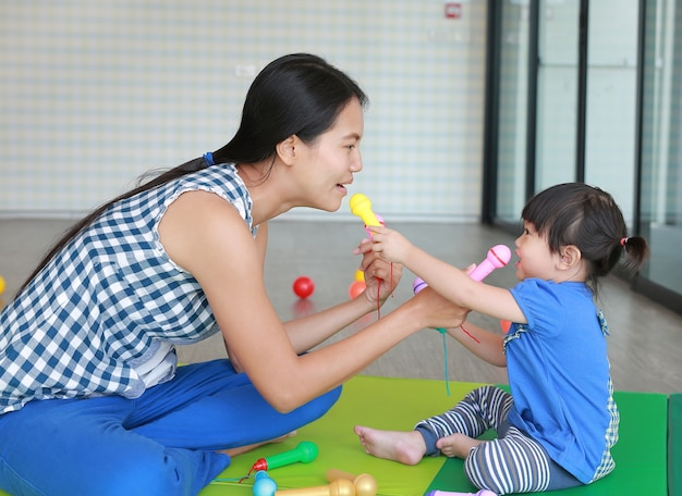 Mãe e bebê fofo asiático menina tocando microfone de plástico no quarto do garoto