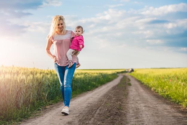 Mãe e bebê menina andando na estrada de cascalho