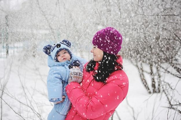 Mãe e bebê menino brincando debaixo da neve. mãe, e, menino bebê, em, a, luminoso, inverno, roupas