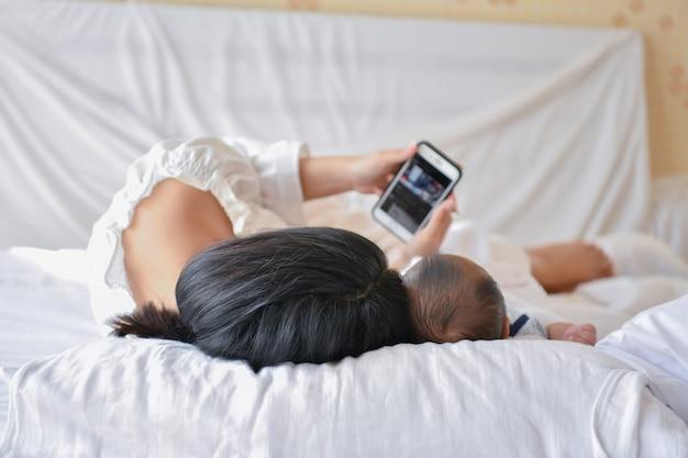 Mãe e bebê menino brincando no quarto. mãe está jogando celular na cama.
