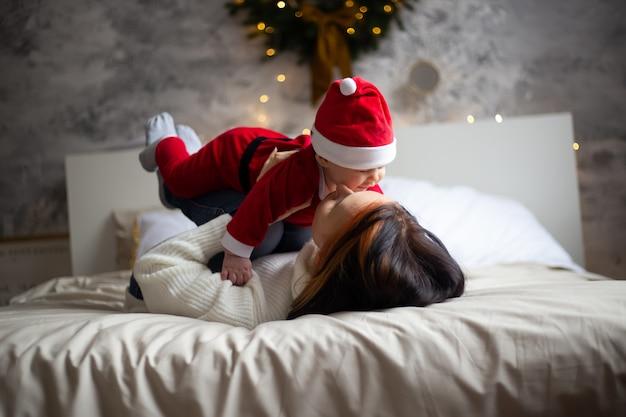 Mãe e bebê menino no natal decorado em casa