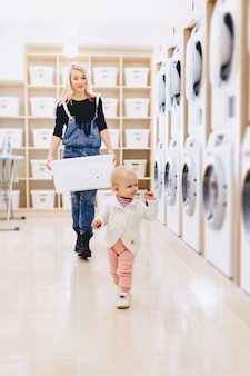 Mãe e bebê na lavanderia levar as coisas e brincar