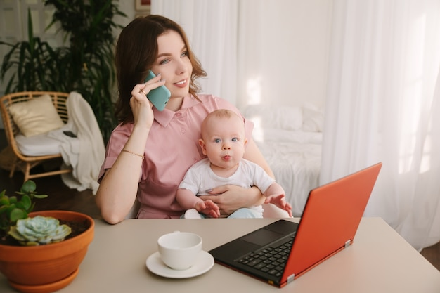 Mãe e bebê no escritório em casa com laptop e telefone