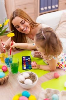 Mãe e bebê pintando ovos de páscoa