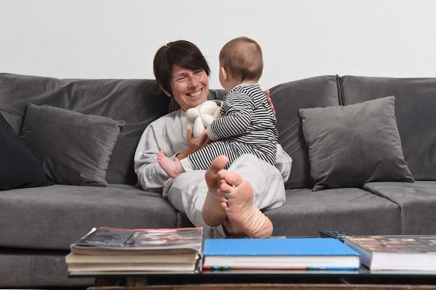 Mãe e bebê relaxados e brincando no sofá