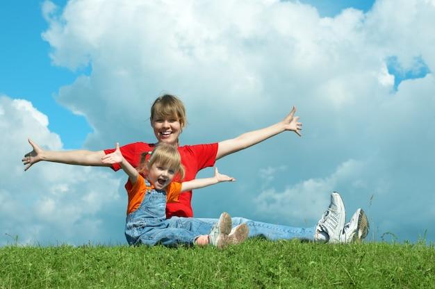 Mãe e bebê sentados na grama e com as mãos abertas sob o céu com nuvens