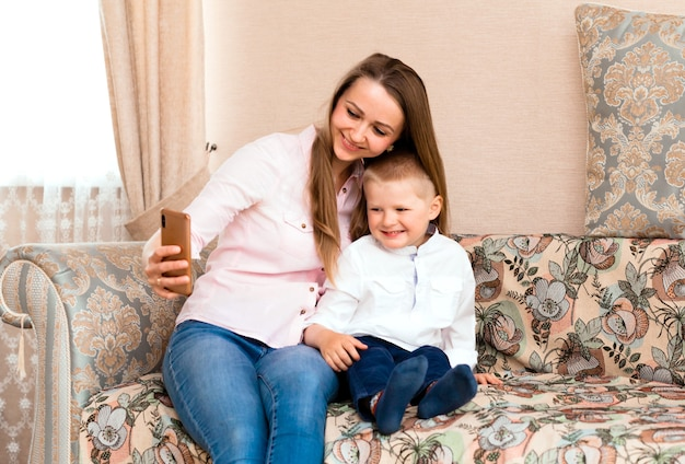 Mãe e bebê tirando uma selfie em uma aconchegante sala de estar. mãe e filho fazem caretas engraçadas e tiram fotos de si mesmos na câmera