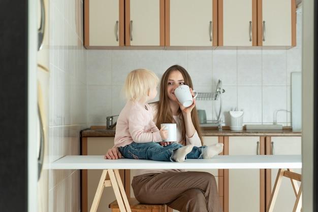 Mãe e bebê tomam café da manhã na cozinha pela manhã. família jovem e feliz.