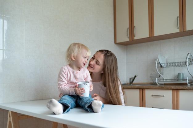 Mãe e comunicação linda garotinha na cozinha. manhã em família.