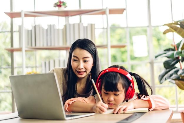 Mãe e criança asiática, menina, aprendendo e olhando para o laptop, fazendo lição de casa, estudando conhecimento com sistema de e-learning de educação online