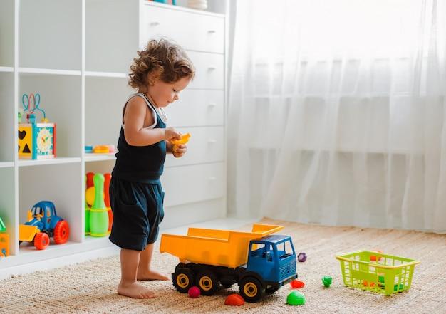 Mãe e criança brincam no chão no berçário. mãe e bebê menino estão fazendo com brinquedos coloridos de plástico.