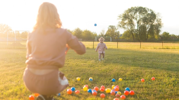 Mãe e criança brincando com bolas de plástico