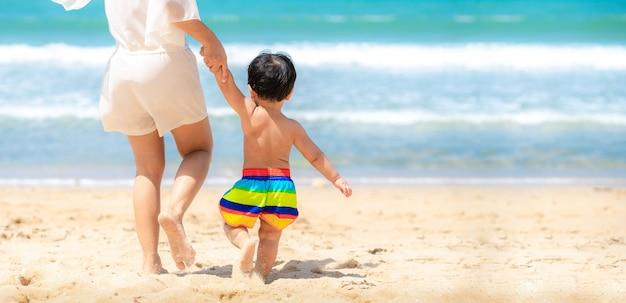 Mãe e criança correm na praia de areia