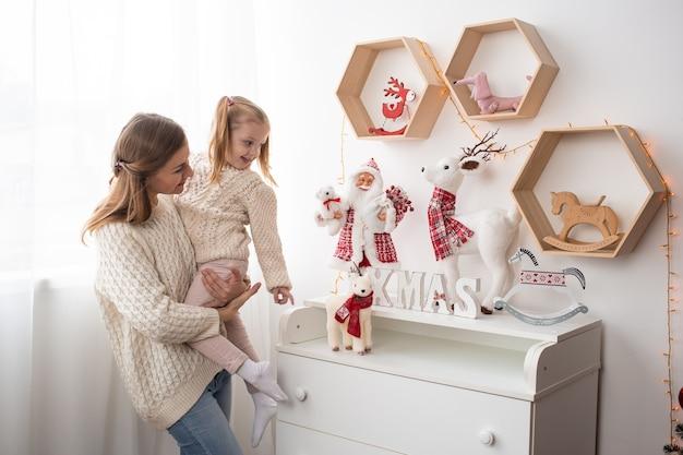 Mãe e criança fofa menina em casa na época do natal