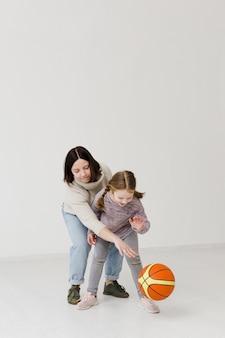 Mãe e criança jogando basquete