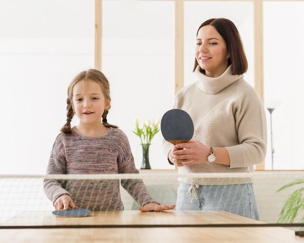 Mãe e criança jogando tênis de mesa