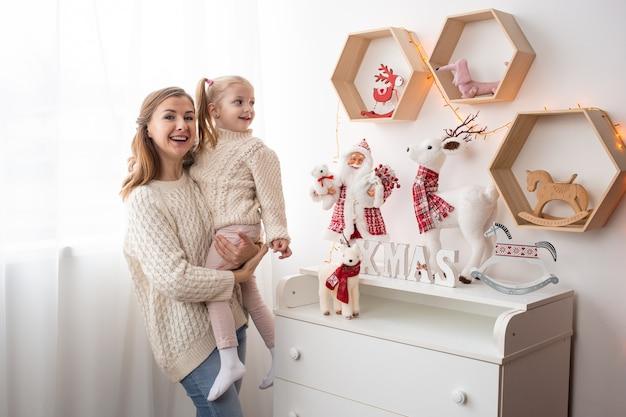Mãe e criança menina em casa na época do natal