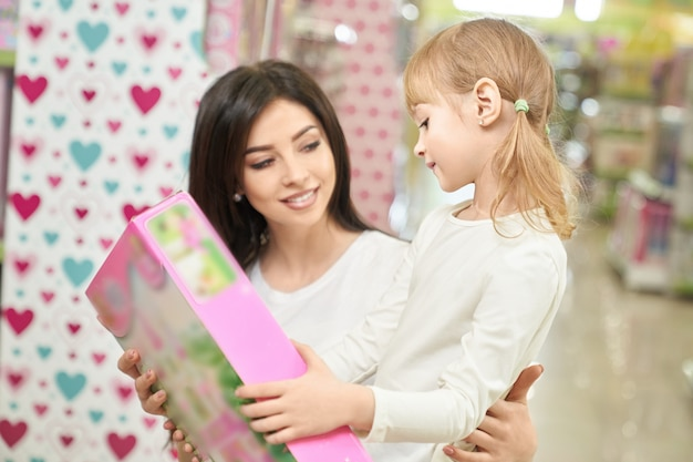 Mãe e criança olhando e escolhendo o brinquedo na loja.