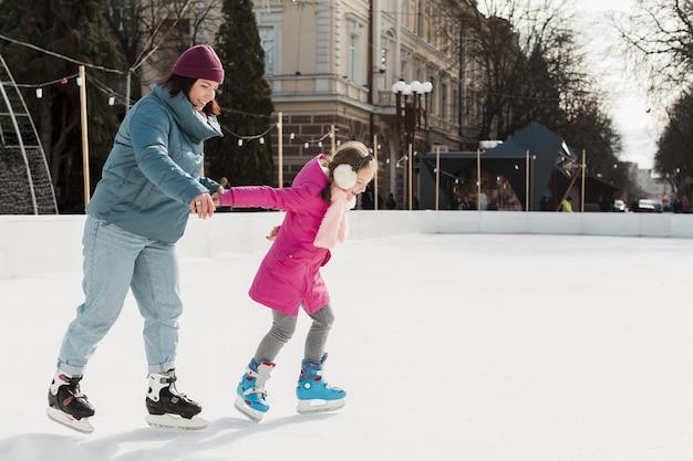 Mãe e criança patinando no gelo