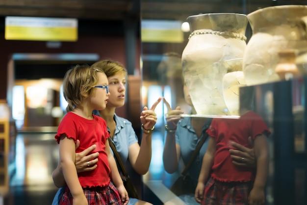 Mãe e criança que procuram amphores antigos no museu