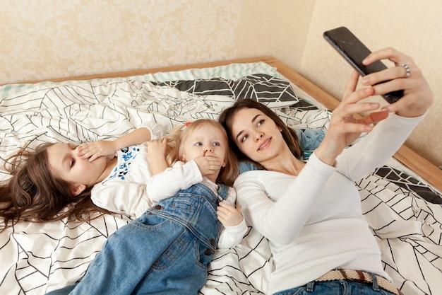 Mãe e crianças tomando selfie