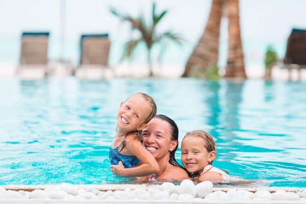 Mãe e dois filhos curtindo férias de verão na piscina de luxo