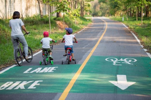Mãe e dois filhos estão andando de bicicleta na ciclovia.