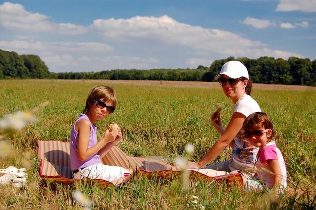 Mãe e dois filhos fazendo piquenique ao ar livre