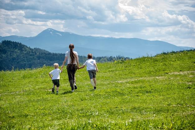 Mãe e dois filhos jovens correndo no campo verde, segurando as mãos em montanhas verdes e céu com nuvens.