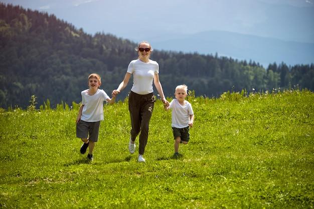 Mãe e dois filhos jovens correndo no campo verde, segurando as mãos em um fundo de floresta verde, montanhas e céu com nuvens.