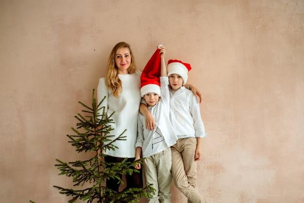 Mãe e dois filhos perto de uma parede rosa e uma árvore de natal. minimalismo.