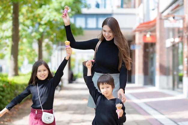 Mãe e dois filhos tomando sorvete com um sorriso ao ar livre