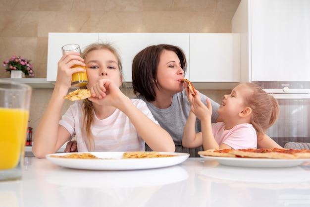 Mãe e duas filhas comendo pizza caseira em uma mesa na cozinha, conceito de família feliz