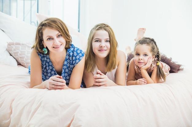 Mãe e duas filhas deitadas felizes e sorrindo em casa no quarto na cama