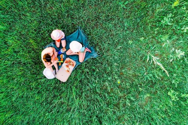 Mãe e duas filhas fazem piquenique com pizza em uma foto aérea de grama verde