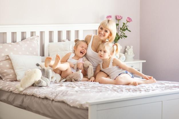 Mãe e duas filhas se divertindo na cama