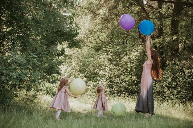 Mãe e duas filhas segurando as mãos circulando.