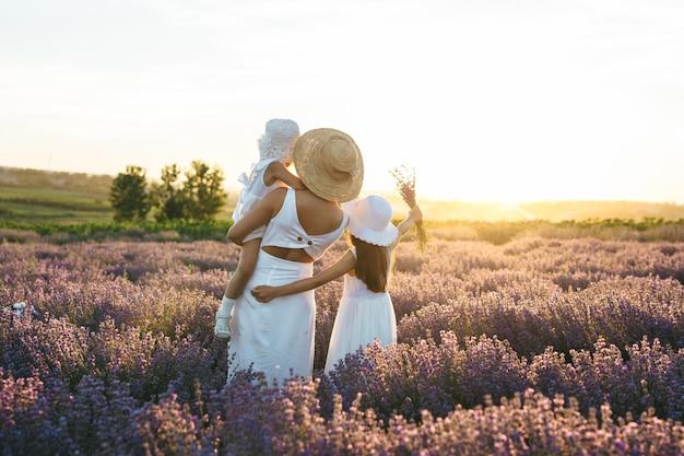 Mãe e duas meninas olham para o pôr do sol no campo de lavanda