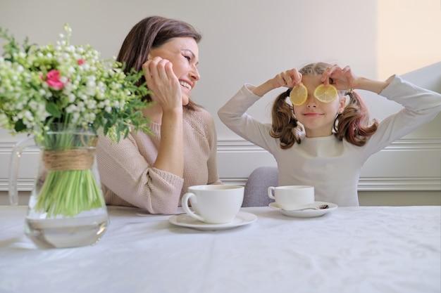 Mãe e filha a beber copos e a comer limão a rir.