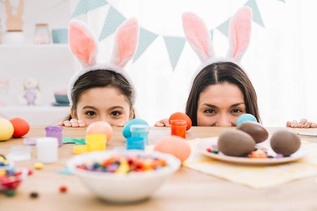 Mãe e filha a espreitar por trás da mesa com ovos de páscoa; confeitaria e cores