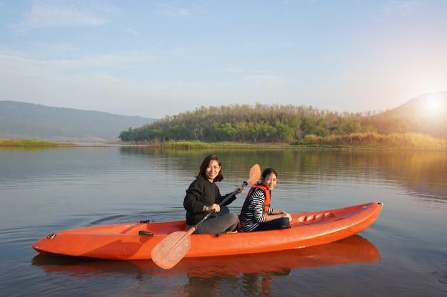 Mãe e filha a remo de barco em águas calmas