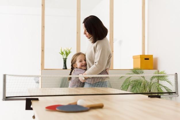 Mãe e filha abraçando dentro de casa